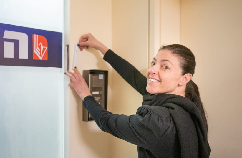 Labor leader Merav Michaeli affixes a Mezuza outside her party's new campaign headquarters (photo credit: Courtesy)