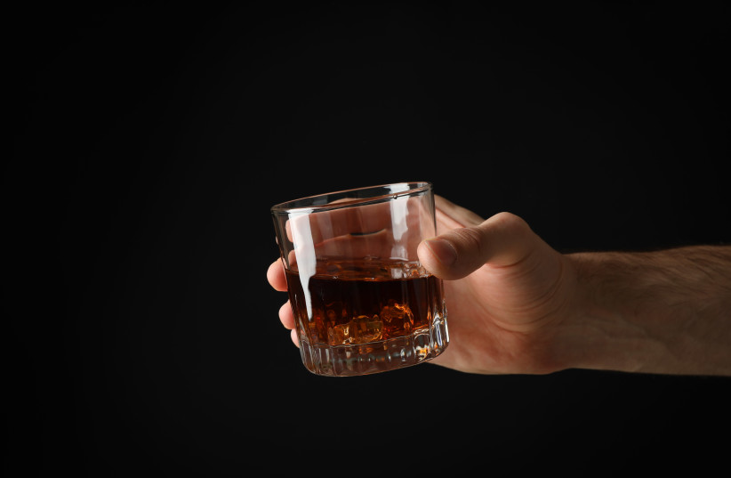 A man holds a glass of scotch. (photo credit: ISTOCK)
