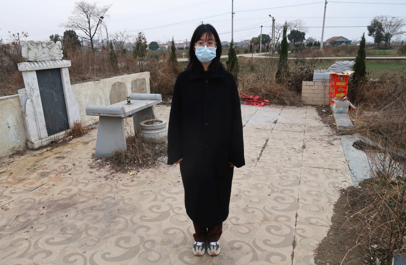 Deng Wei poses for a picture in front of her grandmother's and father's tombs, both of whom died due to complications related to the coronavirus disease (COVID-19), in Wuhan, Hubei province, China January 24, 2021.  (photo credit: REUTERS/MARTIN POLLARD)