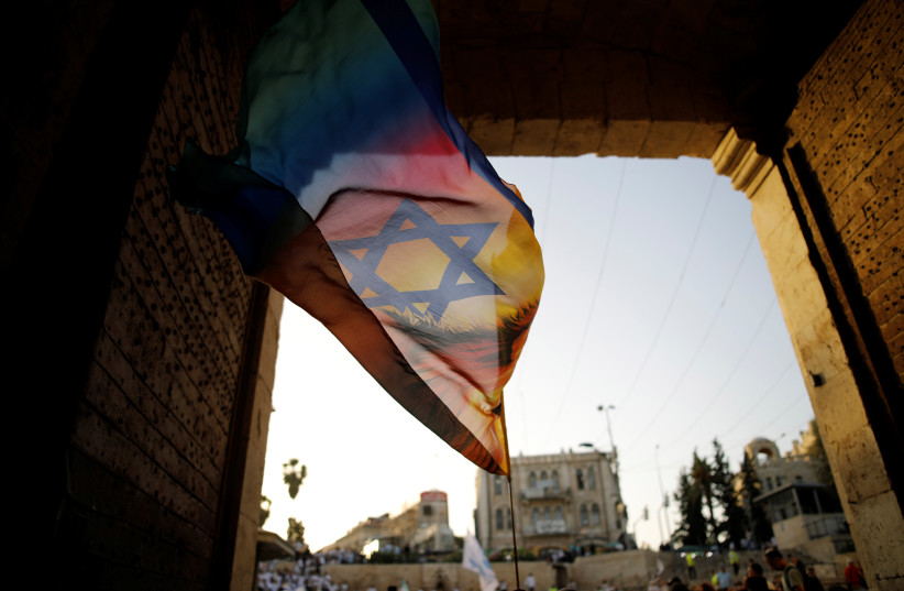 "A Jewish youth waves a flag as he participates in a march marking ""Jerusalem Day"", near Damascus Gate in Jerusalem's Old City June 2, 2019.  (photo credit: REUTERS/AMIR COHEN)"