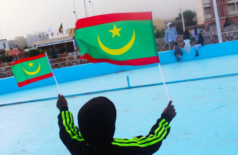A young boy is seen waving Mauritanian flags. (photo credit: Wikimedia Commons)