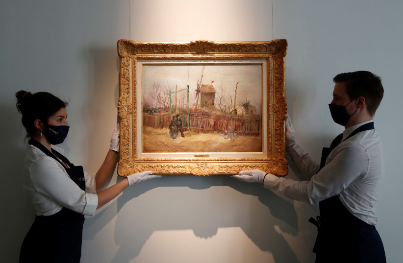 "Sotheby's Paris employees pose with the 1887 painting of a Paris street scene ""Scene de rue a Montmartre"" by Dutch painter Vincent Van Gogh which will be presented to the public for the first time after spending more than a century behind closed doors in the private collection of a French family, Fr (photo credit: CHRISTIAN HARTMANN/REUTERS)"
