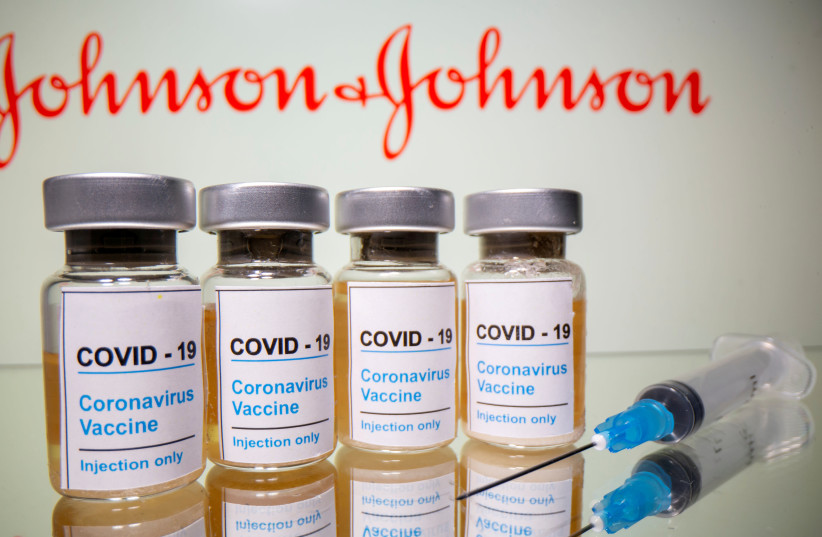 "Vials with a sticker reading, ""COVID-19 / Coronavirus vaccine/ Injection only"" and a medical syringe are seen in front of a displayed Johnson & Johnson logo in this illustration taken October 31, 2020. (photo credit: DADO RUVIC/REUTERS)"
