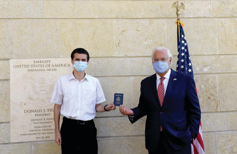 US Ambassador David Friedman presents Menachem Zivotofsky, with a passport (photo credit: DEBBIE HILL/REUTERS)