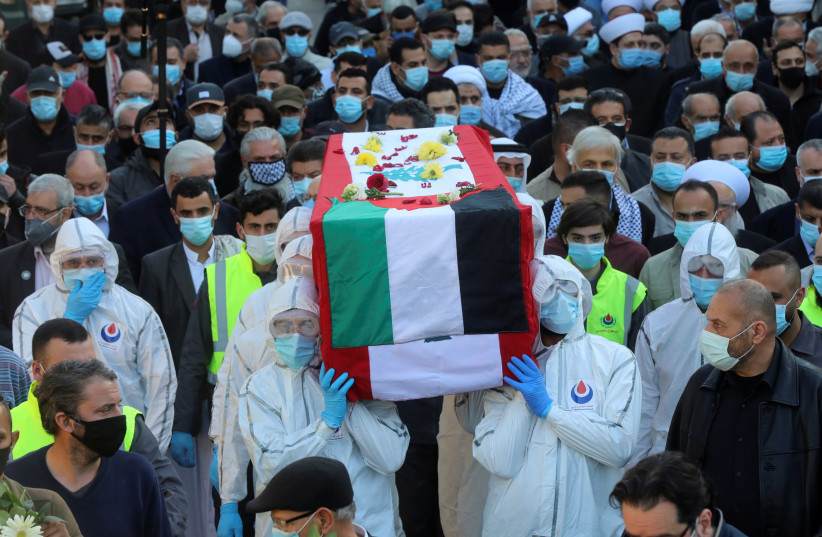 People wearing protective suits carry the coffin of Anis Naccache, a former pro-Palestinian militant, during his funeral in Beirut suburbs, Lebanon February 24, 2021. (photo credit: MOHAMED AZAKIR / REUTERS)