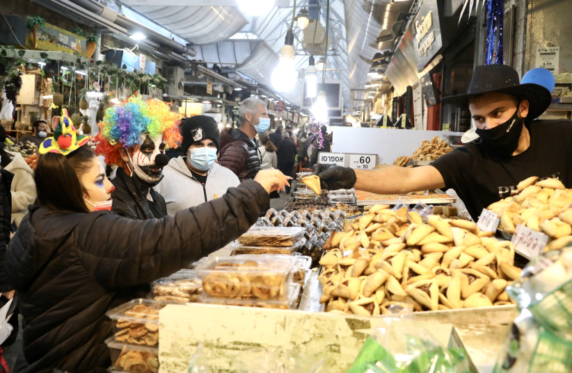 Israelis in Purim costume buy hamentashen from a Mahaneh Yehuda seller. (photo credit: MARC ISRAEL SELLEM/THE JERUSALEM POST)