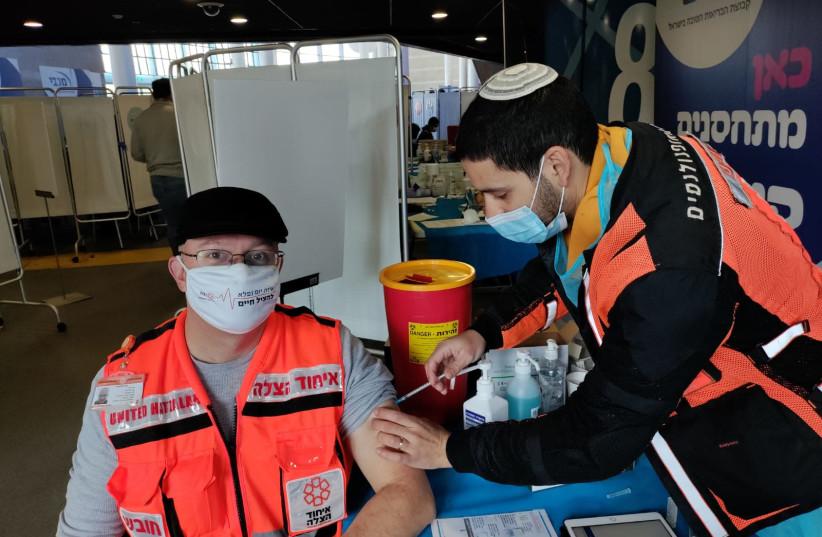 United Hatzalah volunteer vaccinating another in Jerusalem in December (photo credit: UNITED HATZALAH)
