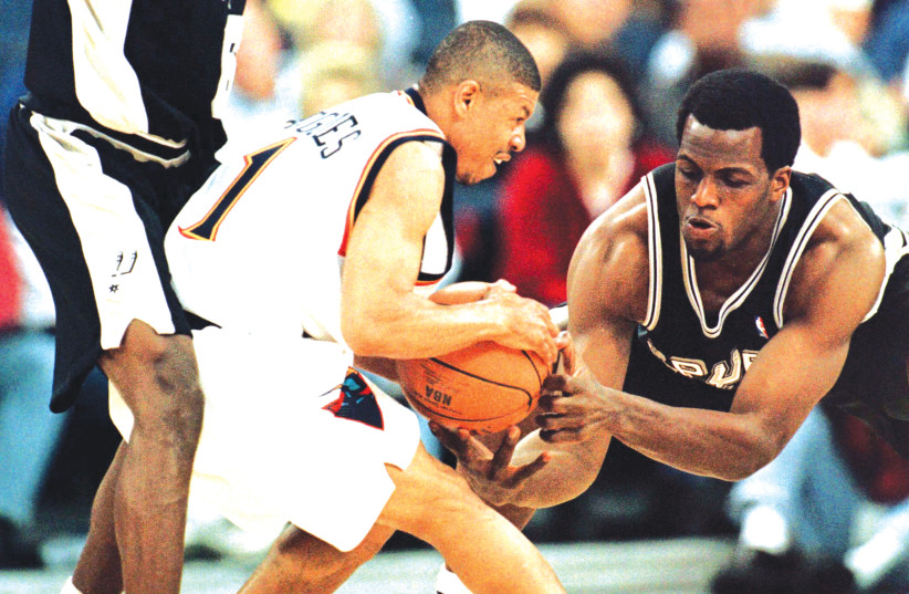 MUGSY BOGUES (center), the NBA's shortest player ever, in action in 1999. While basketball has gone small, the investing world has gone the opposite direction. (photo credit: REUTERS)