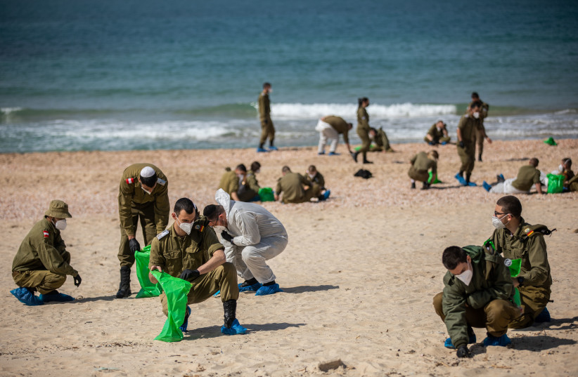 SOLDIERS CLEAN tar off Palmahim beach on Monday, following an offshore oil spill that drenched most of the Israeli coastline. (photo credit: YONATAN SINDEL/FLASH 90)