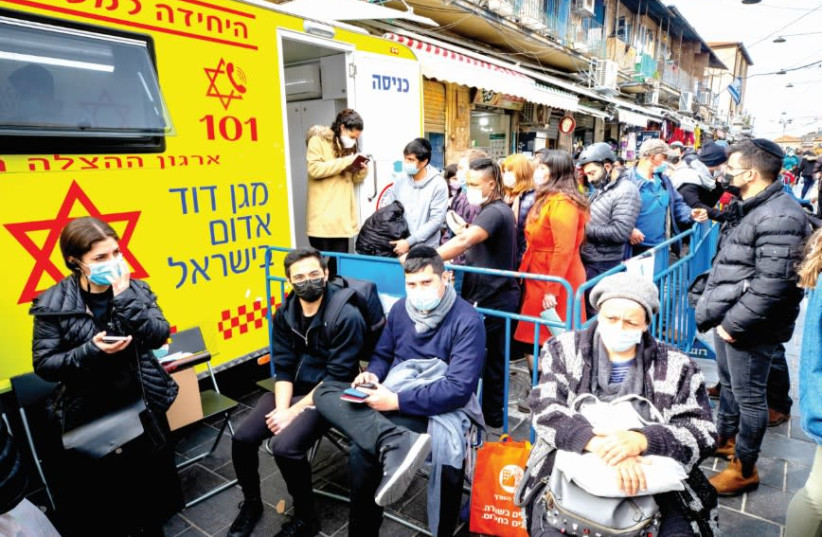 PEOPLE WAIT to receive their COVID-19 vaccine injections outside a mobile Magen David Station at the Mahaneh Yehuda market in Jerusalem, on Monday. (photo credit: OLIVIER FITOUSSI/FLASH90)