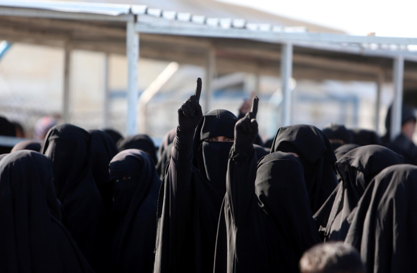 Women gesture as they stand together al-Hol displacement camp in Hasaka governorate, Syria, April 2, 2019. (photo credit: ALI HASHISHO/REUTERS)