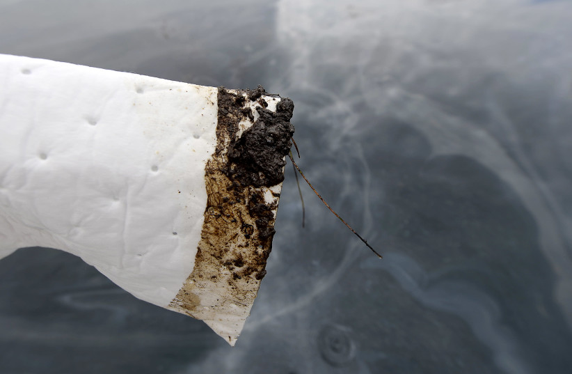 An absorbent is used to show oil slick in the waters off Refugio State Beach on the Californian coast in Goleta, California, United States, May 21, 2015. An oil pipeline that burst along the California coast, fouling pristine beach and stretch of ocean near Santa Barbara, is believed to have spilled (photo credit: KEVORK DJANSEZIAN/REUTERS)