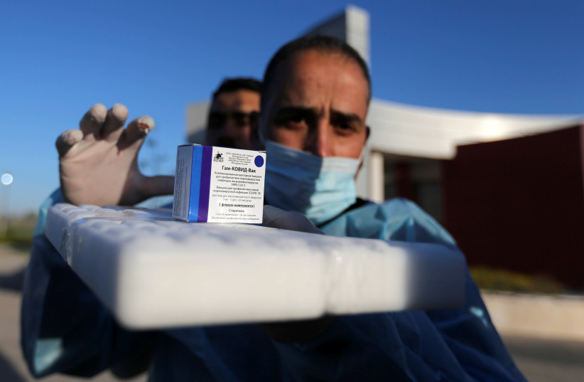 A Palestinian health worker prepares a coronavirus disease (COVID-19) vaccine in Gaza City February 22, 2021.  (photo credit: REUTERS)