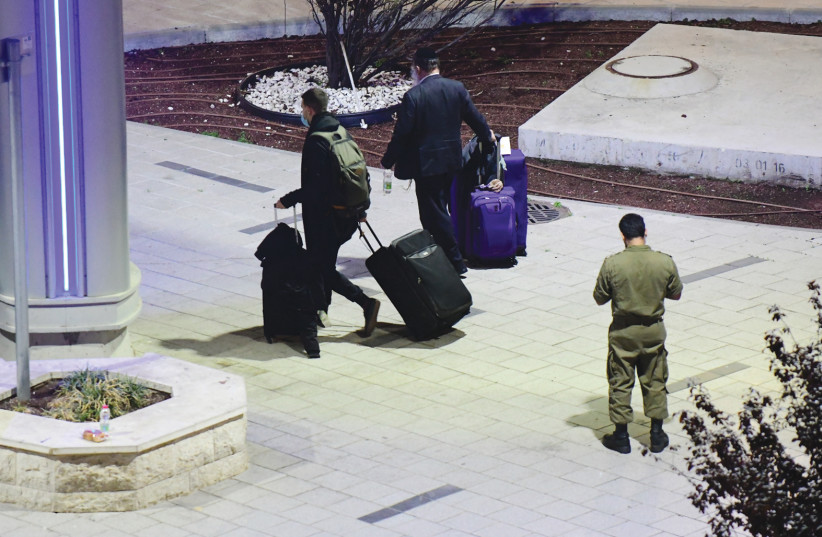 ISRAELI PASSENGERS arrive home after an emergency flight to Ben-Gurion Airport on February 3. (photo credit: TOMER NEUBERG/FLASH90)