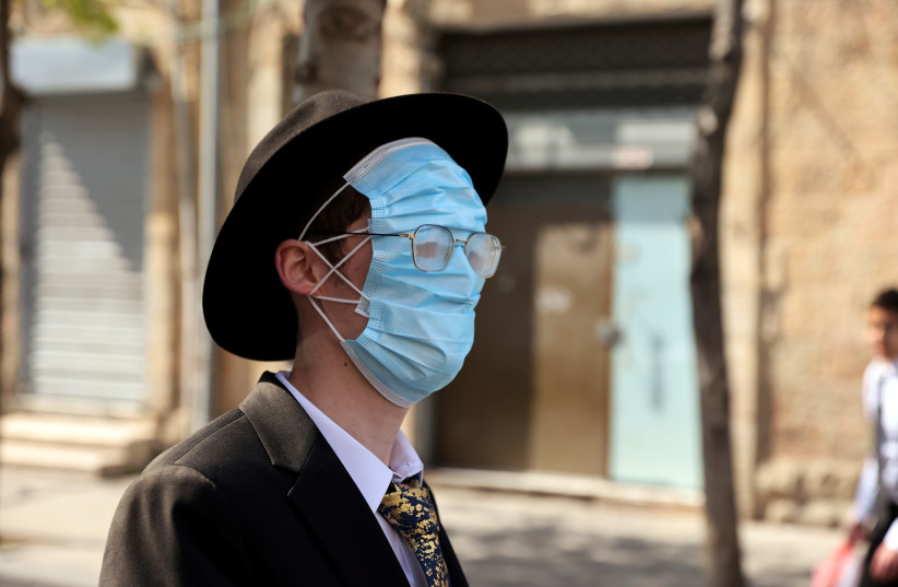 An ultra-Orthodox man wears three masks over his face while celebrating Purim amid coronavirus disease (COVID-19) restrictions in Jerusalem February 28, 2021  (photo credit: RONEN ZVULUN/REUTERS)