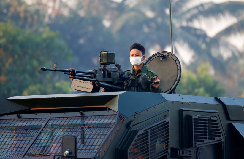A soldier is seen on top of an armored vehicle believed to be made by Gaia Automotive Industres as he rolls through the streets of Naypyitaw, Myanmar, February 15, 2021.  (photo credit: REUTERS/STRINGER)
