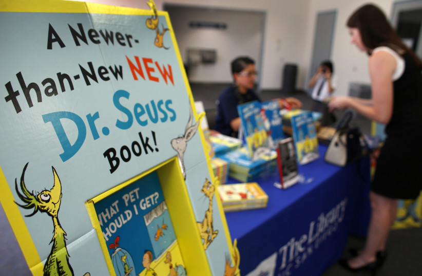 "A woman purchases the new release of the Dr. Seuss book ""What Pet Should I Get?"" after waiting in line at the University of California San Diego's Geisel Library in San Diego, California July 28, 2015. (photo credit: MIKE BLAKE/ REUTERS)"