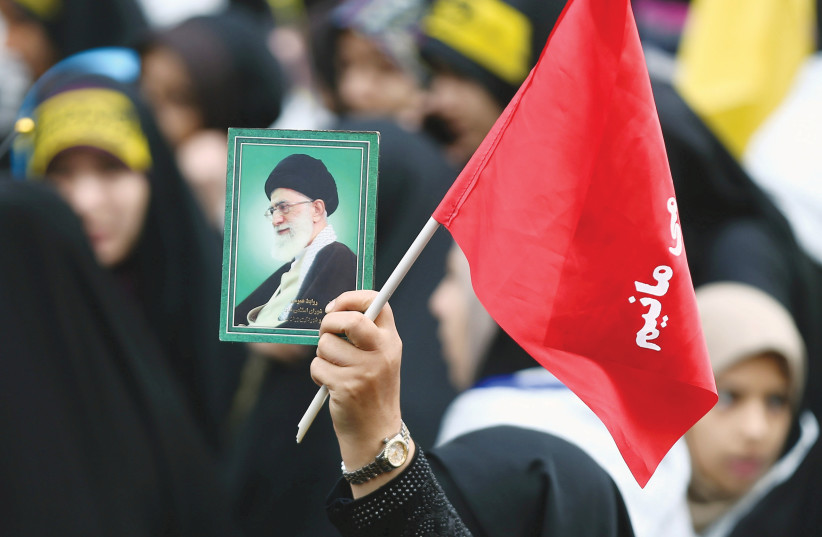 A WOMAN holds a picture of Ayatollah Ali Khamenei, at an anti-US demonstration near the old US embassy in Tehran in 2019. (photo credit: NAZANIN TABATABAEE/REUTERS)