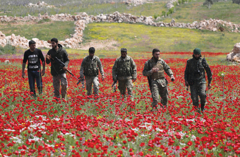 TURKISH-BACKED FIGHTERS walk through the southern countryside of Syria's Idlib Province in April. (photo credit: KHALIL ASHAWI / REUTERS)