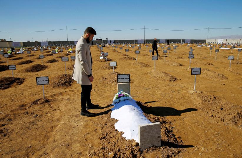 Thikran Kamiran Yousif, 22, visits his father's grave in Kojo, Iraq February 7, 2021.  (photo credit: REUTERS/THAIER AL-SUDANI)