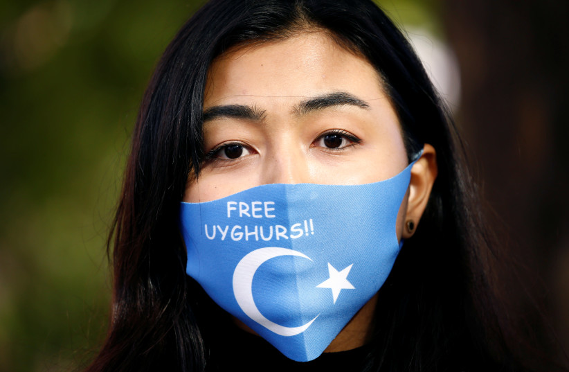 A woman wearing a mask with a Uyghur flag takes part in a rally during China's Foreign Minister Wang Yi's visit in Berlin, Germany September 1, 2020.  (photo credit: REUTERS/MICHELE TANTUSSI)