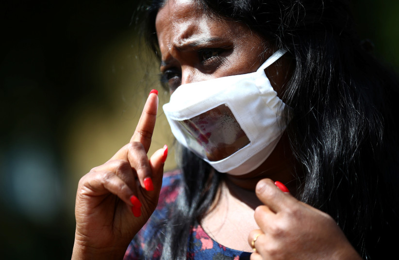 Director of Empowering Deaf Society Mangai Sutharsan uses sign language to communicate whilst wearing a partially transparent mask, following the coronavirus disease (COVID-19) outbreak in Ilford, London, Britain, July 29, 2020. (photo credit: HANNAH MCKAY/ REUTERS)