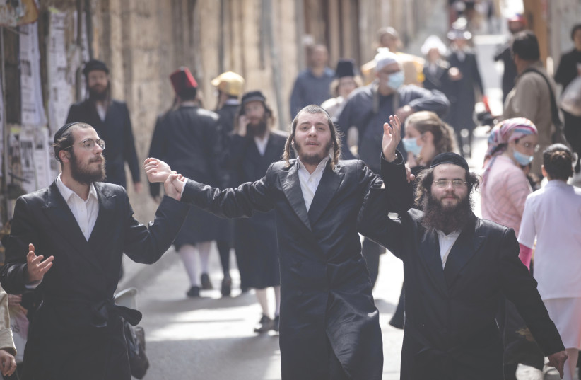 MEN CELEBRATE Purim in Jerusalem's Mea She'arim neighborhood on Sunday. (photo credit: YONATAN SINDEL/FLASH 90)