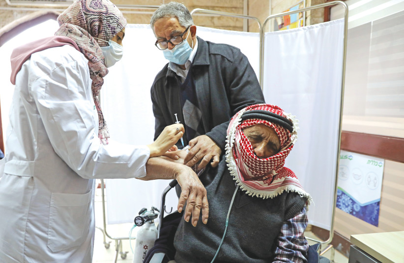 A MAN is helped by his son as he receives a COVID-19 vaccination at a clinic in east Jerusalem in December. (photo credit: AMMAR AWAD/REUTERS)