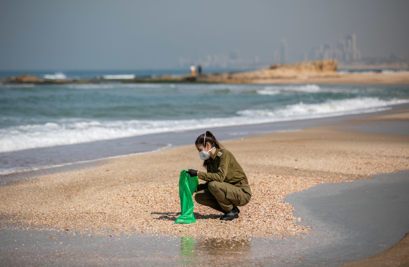Israeli soldiers clean tar off the Palmachim beach following an offshore oil spill which drenched most of the Israeli coastline, February 22, 2021 (photo credit: YONATAN SINDEL/FLASH 90)