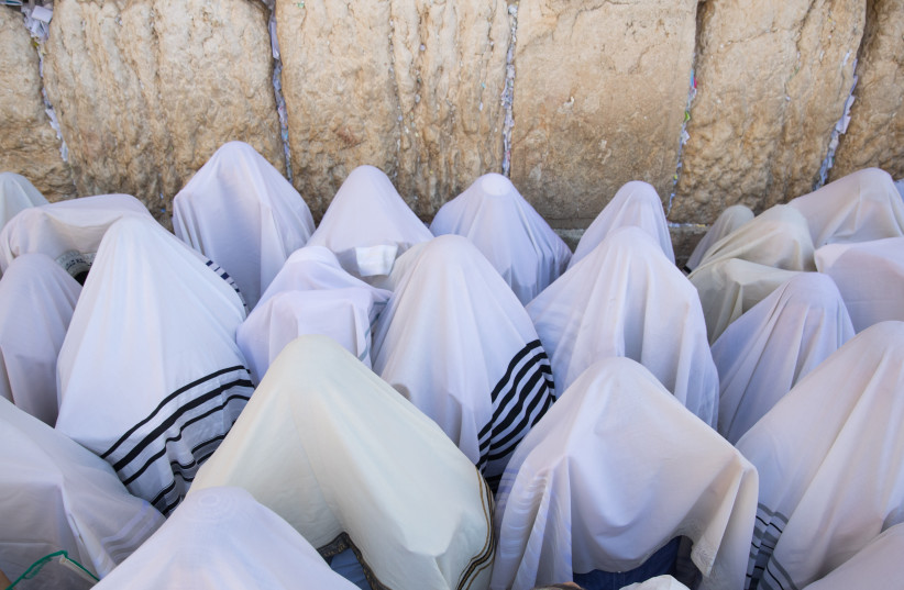 PRAYING DURING the priestly blessing at the Kotel, Sukkot 2018. (photo credit: NOAM REVKIN FENTON/FLASH90)
