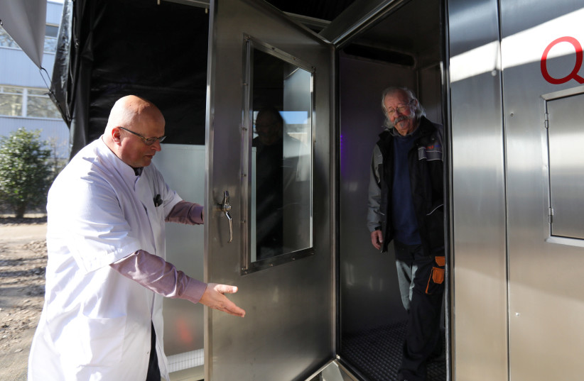 Peter van Wees opens the door so John Moritz can exit the quick breath analyzer cabin that tests for the coronavirus disease (COVID-19) at a testing location in Amsterdam, Netherlands March 1, 2021. (photo credit: REUTERS/EVA PLEVIER)