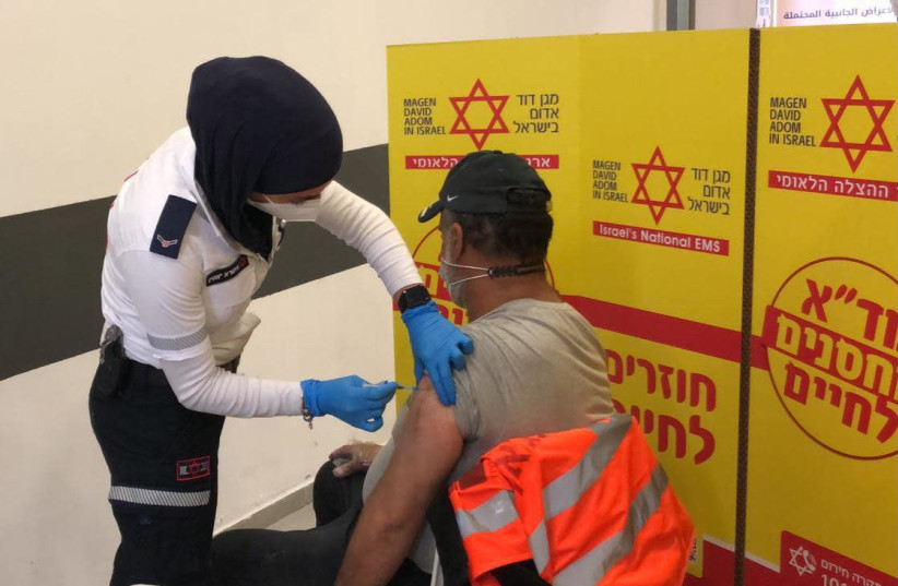 Palestinian workers getting vaccinated against the coronavirus, March 4, 2021.  (photo credit: COGAT)