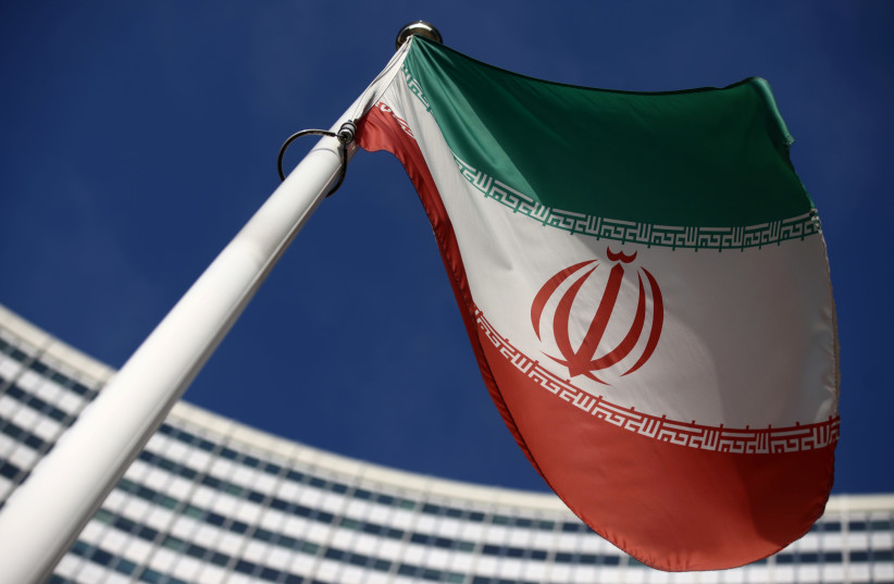 The Iranian flag waves in front of the International Atomic Energy Agency (IAEA) headquarters, before the beginning of a board of governors meeting, amid the coronavirus disease (COVID-19) outbreak in Vienna, Austria, March 1, 2021. (photo credit: REUTERS/LISI NIESNER)