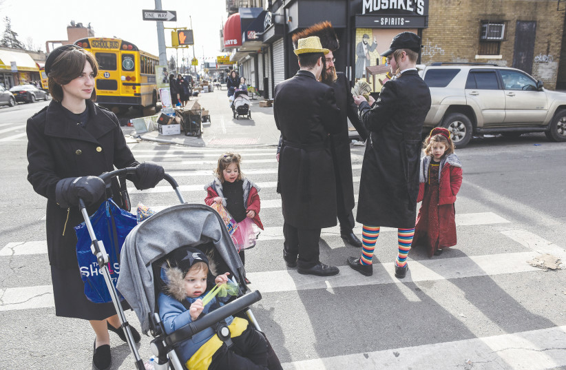 A FAMILY pauses in the street as people celebrate Purim in Brooklyn earlier this month. (photo credit: STEPHANIE KEITH/REUTERS)