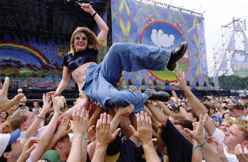 Victoria Rose, 17, enjoys a ride across the crowd, Woodstock 1994. She lost her clothes crowd-surfing. (photo credit: REUTERS)