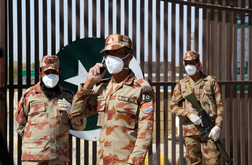 Paramilitary soldiers wear face masks as they stand in front of a closed gate of Pakistan's border post, after Pakistan sealed its border with Iran as a preventive measure following the coronavirus outbreak, at the border post in Taftan, Pakistan February 25, 2020. (photo credit: REUTERS/NASEER AHMED)