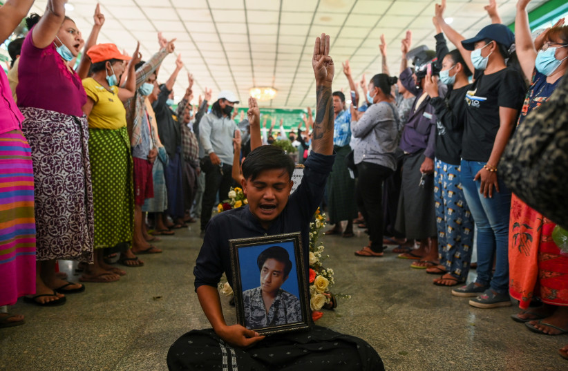 People flash a three-finger salute as they attend the funeral of victims shot dead during the anti-coup protest in Yangon, Myanmar, March 5, 2021. (photo credit: STRINGER/ REUTERS)