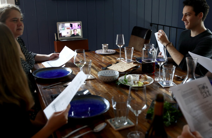 A family celebrates the Passover Seder with other family members joining via Zoom, April 8, 2020. (photo credit: EZRA SHAW/GETTY IMAGES)