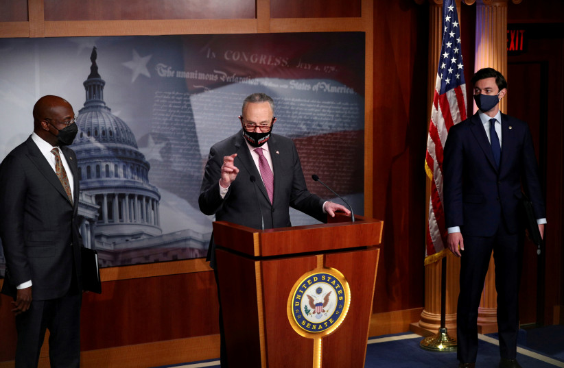 Senate Majority Leader Chuck Schumer (D-NY) delivers remarks beside Senators Jon Ossoff and Raphael Warnock (D-GA) on COVID-19 relief, amid the coronavirus disease (COVID-19) outbreak, on Capitol Hill in Washington, US, February 11, 2021.  (photo credit: REUTERS/TOM BRENNER/FILE PHOTO)