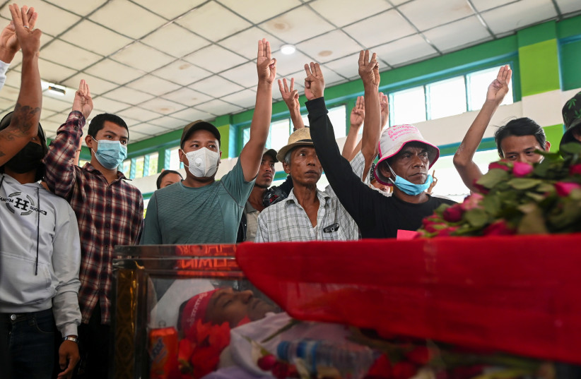 People flash a three-finger salute in front of a casket with a body of a victim who was shot dead during the anti-coup protest, in a cemetery at the outskirts of Yangon, Myanmar, March 5, 2021.  (photo credit: STRINGER/ REUTERS)