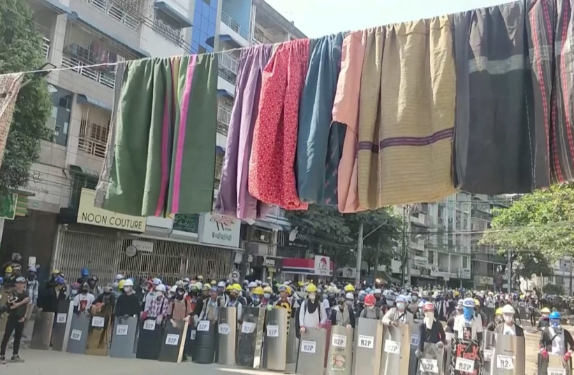 Traditional clothes hang on a rope as protesters holding shields stand in line in the background during a protest against the military coup in Yangon, Myanmar March 6, 2021 in this still image obtained by Reuters from a video. (photo credit: REUTERS)