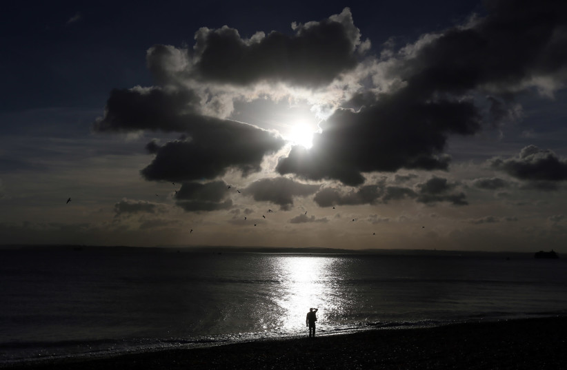A man looks out to sea in Portsmouth (photo credit: STEFAN WERMUTH/REUTERS)