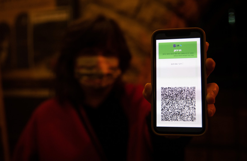 A woman shows her green passport at the Khan theater in Jerusalem on February 23, 2021. (photo credit: YONATAN SINDEL/FLASH90)