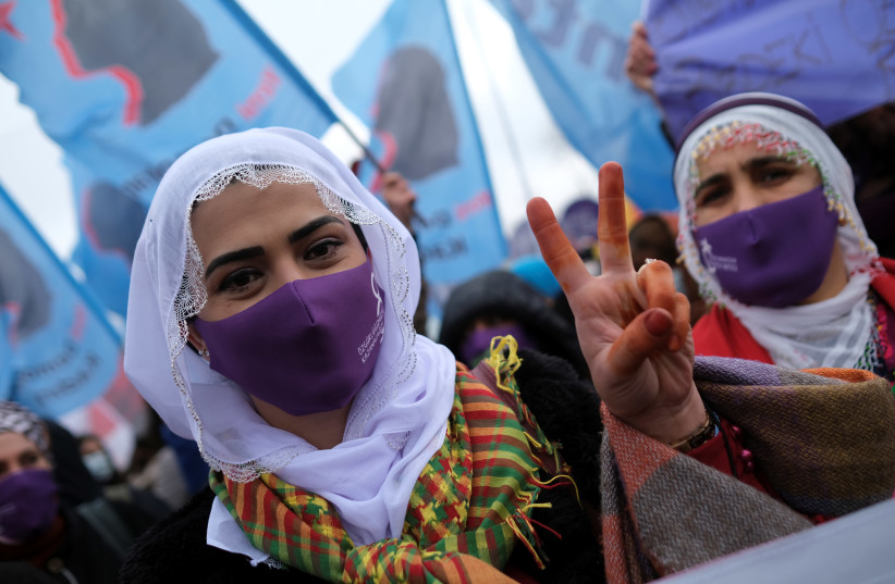 A demonstrator wearing a face mask to prevent the spread of the coronavirus disease (COVID-19) flashes the V sign during a rally ahead of the International Women's Day in Istanbul, Turkey March 6, 2021 (photo credit: REUTERS/MURAD SEZER)