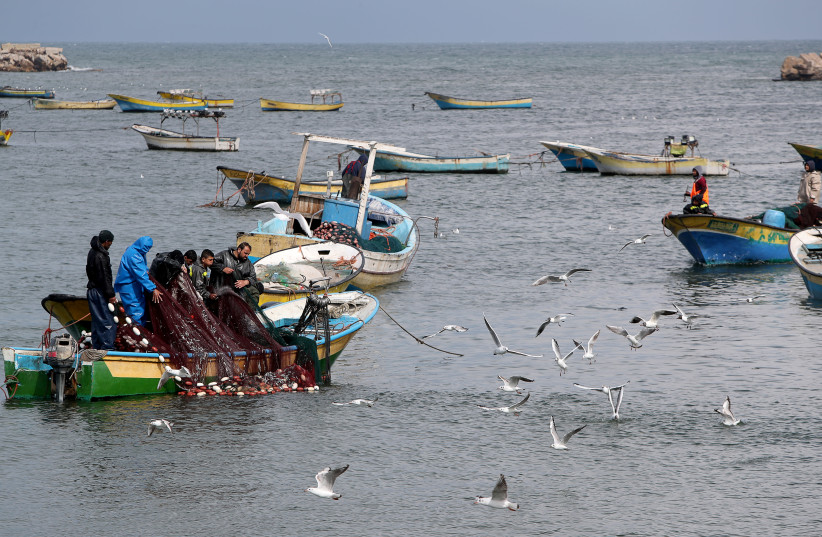 Palestinian fishermen riding a boat cast their net as birds fly off the coast of Gaza City February 19, 2020 (photo credit: REUTERS/MOHAMMED SALEM)