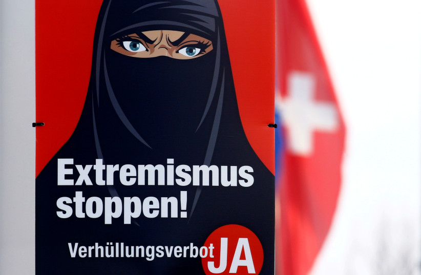 "A Swiss national flag flies behind a poster of the initiative committee against wearing the burqa (Verhuellungsverbot) reading ""Stop extremism! Veil ban -Yes"" in Berikon, Switzerland February 12, 2021. On March 7 Switzerland's voters will decide about a nationwide veil ban. (photo credit: REUTERS/ARND WIEGMANN/FILE PHOTO)"
