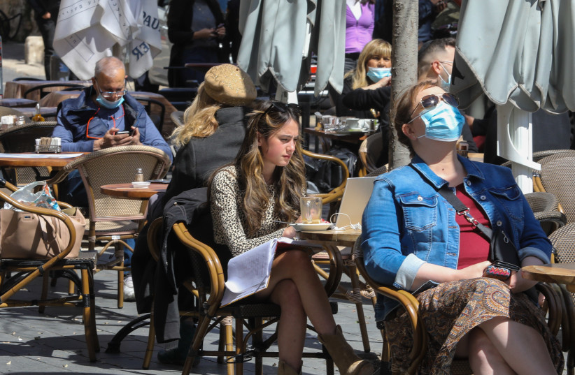 People sit and drink coffee in the sun as Israel reopens its economy after COVID-19 restrictions   (photo credit: MARC ISRAEL SELLEM)