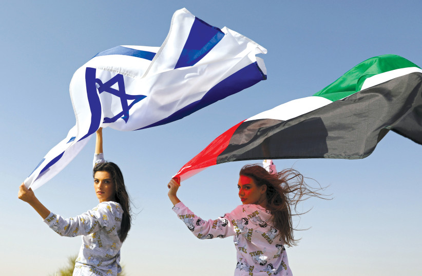 Israeli model May Tager, holding an Israeli flag, poses with Dubai model Anastasia, holding an Emirati flag, during a photo shoot for FIX's Princess Collection in Dubai in September, 2020 (photo credit: CHRISTOPHER PIKE/REUTERS)