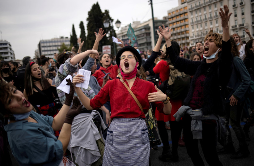 People dance and sing during a demonstration to mark International Women's Day in front of the parliament building in Athens, Greece, March 8, 2021.  (photo credit: REUTERS/ALKIS KONSTANTINIDIS)