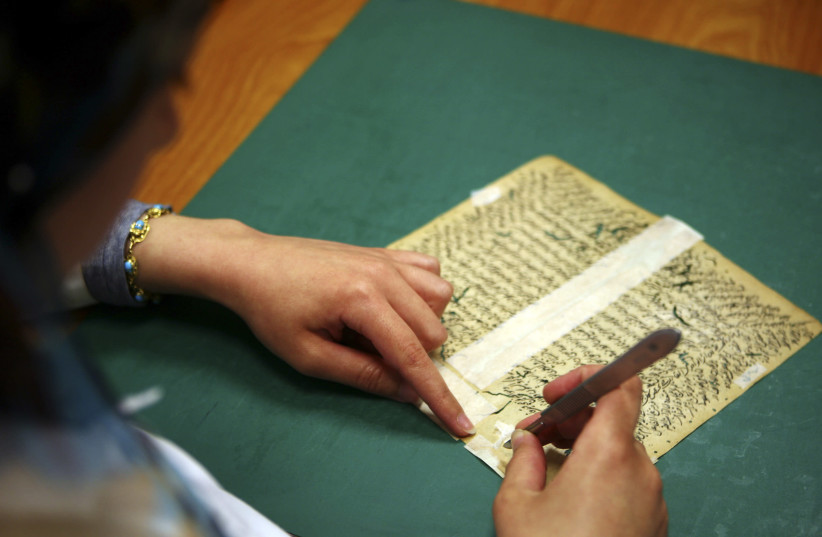 An Egyptian librarian fixes a rare book in the Restoration Laboratory in Alexandria Library (photo credit: REUTERS)